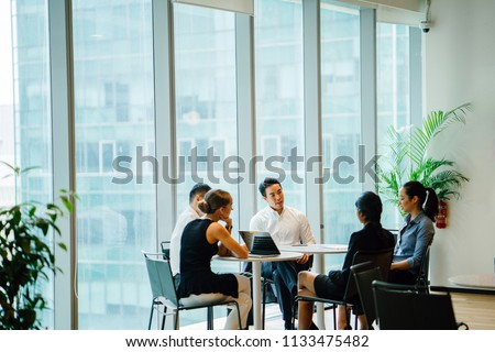 A diverse team sit around a table in a meeting room to have a business meeting to discuss plans. The group is international with Asian and White team members and they are all professionally dressed. #1133475482