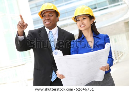 A diverse  woman and man working as architects on a construction site (Focus on Woman) - stock photo