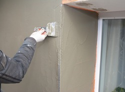 A DIYer, homeowner or professional is applying the final coat of render within the window area using spatula in the external wall insulation process.