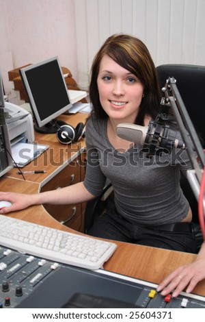 A DJ is in front of a mic in the broadcasting studio