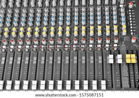A DJ mixer close up. Equalizer background. Many knobs for special sound effects, echo, reverb, volume, etc.