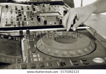 A DJ mixer is a type of audio mixing console used by Disc jockeys (DJs) to control and manipulate multiple audio signals. DJ performing. With one hand he is manipulating a vinyl record on a turnable.