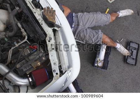 A do-it-yourselfer repairs his car/Man repairing his car/A man beneath his car does repair work.