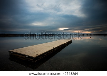 A dock in a lake with the reflection of the sky