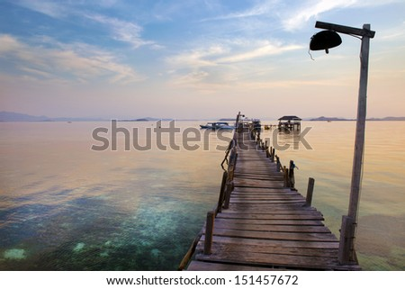 A dock leads to the ocean on a sunset at a tropical resort in Indonesia