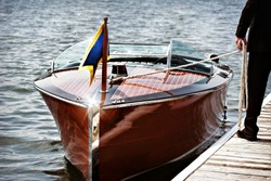 A docked vintage wooden motor boat.  A man stands on the dock holding the mooring line.
