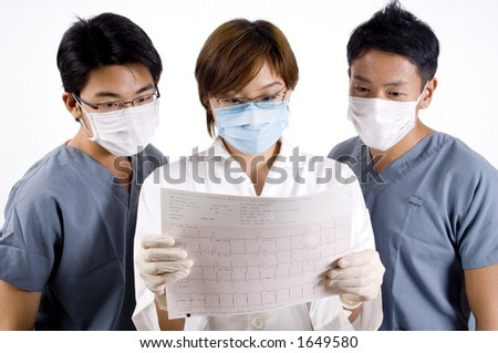 A doctor and two assistants examine the printout from an ecg machine