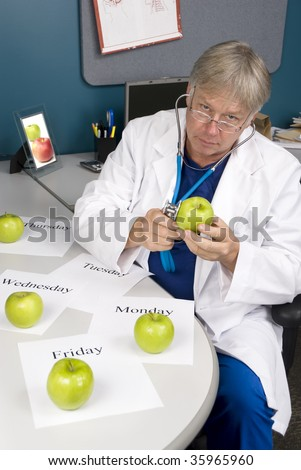A doctor examines an apple with his stethoscope.  Image is useful for any healthy diet or eating inference.