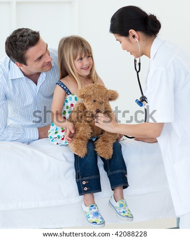 A doctor examining smiling child and playing with a teddy bear in the hospital