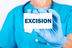A doctor in blue medical uniform holds a card with the name of the diagnosis, the word EXCISION. Medical concept.