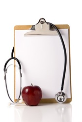 A doctor or nurses clipboard with a stethoscope and a red apple and a blank sheet of notebook paper for information or copy space.  Healthcare of health concept