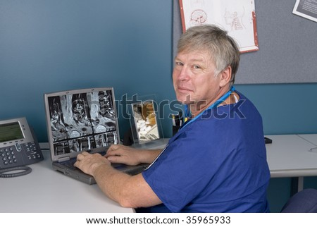 A doctor reviews an MRI on his laptop.  Good for using technology to review imagery as opposed to hard film MRI's.