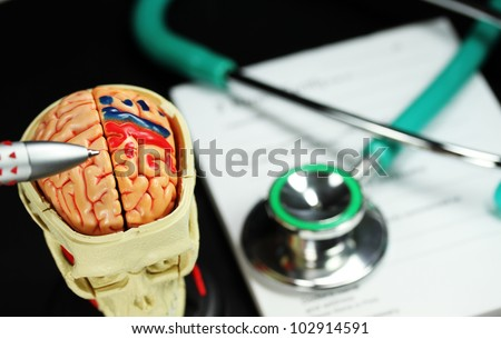 A doctor�s desk showing a green stethoscope and pen, on a sick certificate pad, with the other doctors tools of  and model of a human skull, with the Doctors pen pointing to where the problem is.