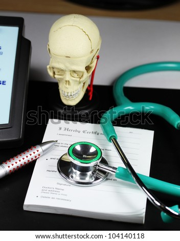 A doctor�s desk showing a green stethoscope and pen, resting on a sick certificate pad, with the other doctors tools of the trade on desk including a blood pressure machine and model of a human skull.