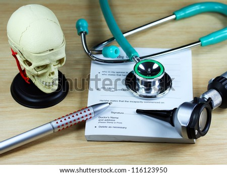 A doctor�s desk showing a green stethoscope and pen, resting on a sick certificate pad, with the other doctor�s tools of the trade on desk including a model of a human skull.