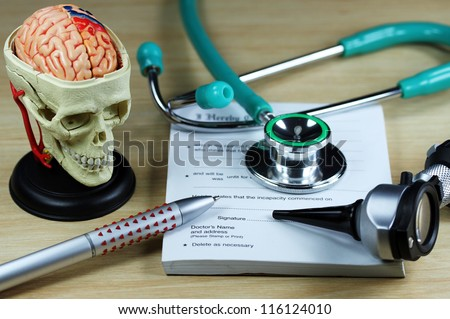 A doctor�s desk showing a green stethoscope and pen, resting on a sick certificate pad, with the other doctor�s tools of the trade on desk including a model of a human skull, with the brain exposed.