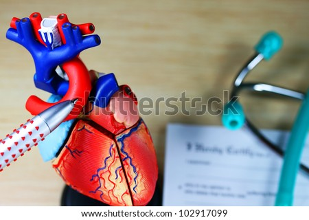 A doctor�s desk showing a green stethoscope on a sick certificate pad in the background, and in the foreground the doctors pen point to a model of the heart, indicating where the patients problem is.