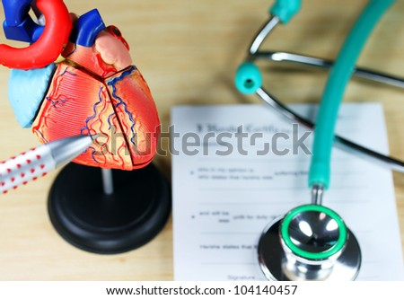 A doctor�s desk showing a green stethoscope, resting on a sick certificate pad in the background, and in the foreground the doctor�s pen point to a model of the heart, indicating patient�s problem is.