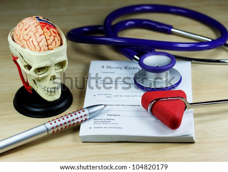 A doctor�s desk showing a purpe stethoscope and pen, resting on a sick certificate pad, with the other doctor�s tools of the trade on desk including a model of a human skull and a patella hammer.
