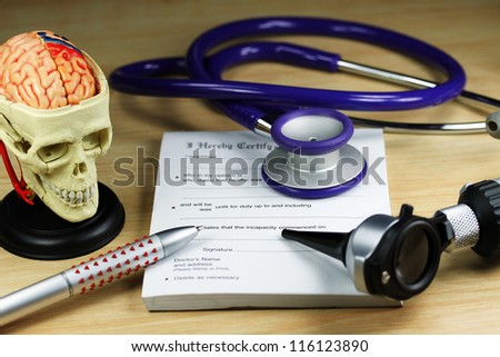 A doctor�s desk showing a purple stethoscope and pen, resting on a sick certificate pad, with the other doctor�s tools of the trade on desk including a model of a human skull, with the brain exposed.