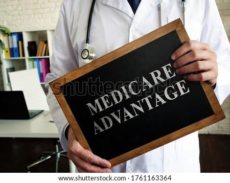 A Doctor shows a tablet Medicare advantage. Сток-фото ©