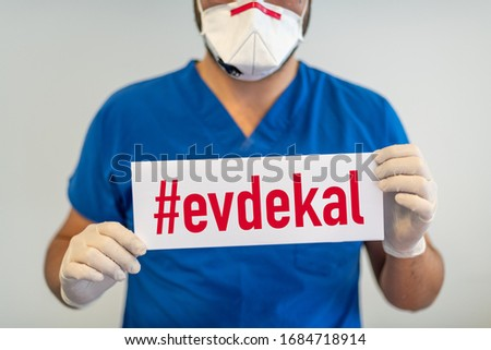 A doctor with a paper with evde kal (Turkish - English translate: stay at home) holding on hand, protect from Coronavirus or Covid-19 epidemic Stok fotoğraf ©