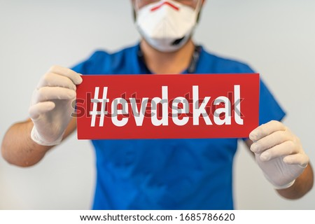 A doctor with a red paper with evde kal (Turkish - English translate: stay at home) holding on hand, protect from Coronavirus or Covid-19 epidemic Stok fotoğraf ©