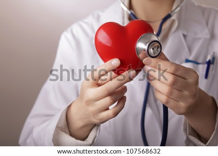 A doctor with stethoscope examining red heart, isolated on grey  background
