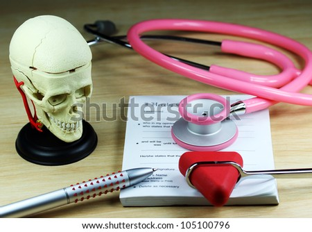 A doctors desk showing a green stethoscope and pen, resting on a sick certificate pad, with the other doctors tools of the trade on desk including a patella hammer and model of a human skull.