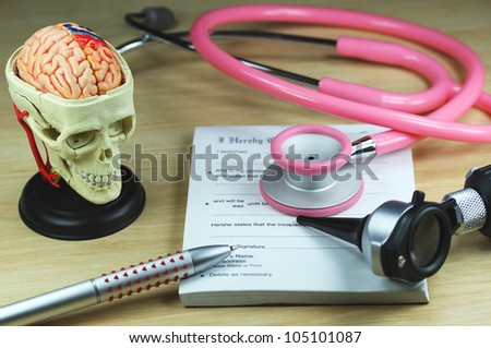 A doctors desk showing a green stethoscope and pen, resting on a sick certificate pad, with the other doctors tools of the trade on desk including a model of a human skull, with the brain exposed.