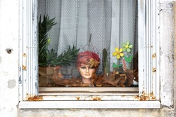 A doll's head with dry leaves, cacti and plastic flowers hangs in a window in Venice