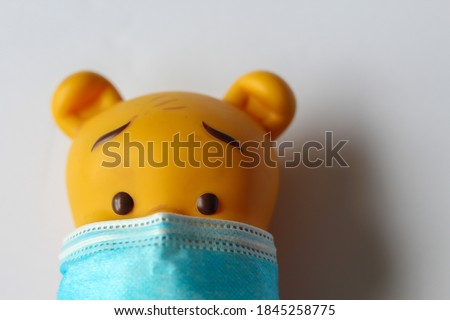 Photo of  A doll wearing COVID19 mask and maintaining safety , background with light color