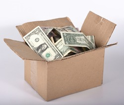 A dollar and other banknotes bulging out of a cardboard box. A cardboard box full of money on a white background