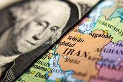 A Dollar bill (figuring George Washington) on top of a map of Iran