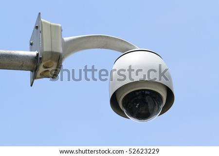 A dome-type security camera against a clear blue sky