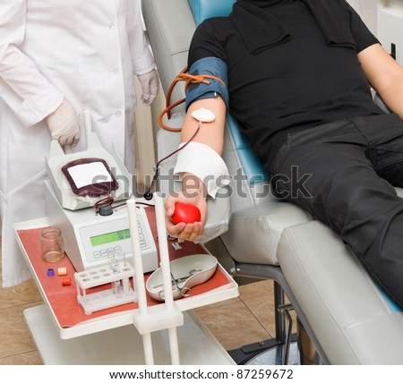 a donor in an armchair donates blood at hemotransfusion station
