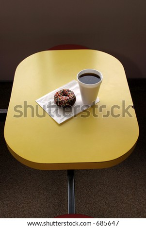 a donut and black coffee in a donut shop
