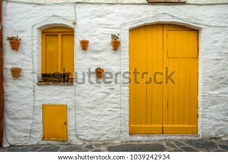 a door and two yellow windows with earthen pots hanging on the white facade