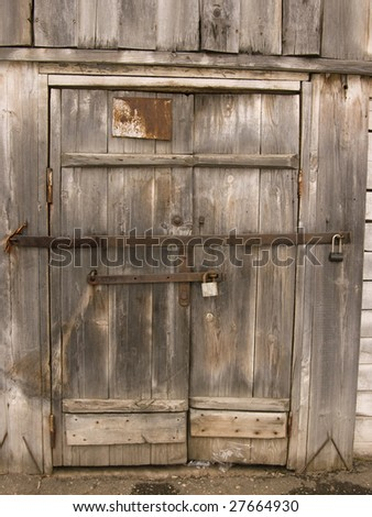 A door of a ramshackle woodshed with two padlocks