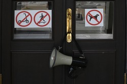 A door with a gold-plated handle; a loudspeaker hangs on the door handle; warning signs with pictogram are pasted on the door