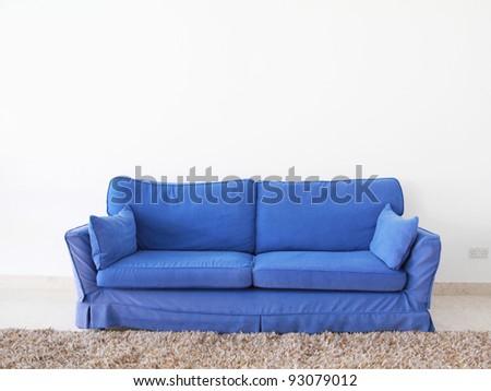 a double blue sofa on a blank wall