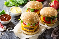 A double burger with a meat cutlet and vegetables is served with cheese sauce and ketchup. Delicious fresh homemade double cheeseburger on a wooden kitchen table. Street food, fast food.
