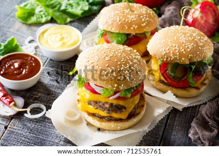 A double burger with a meat cutlet and vegetables is served with cheese sauce and ketchup. Delicious fresh homemade double cheeseburger on a wooden kitchen table. Street food, fast food. #712535761