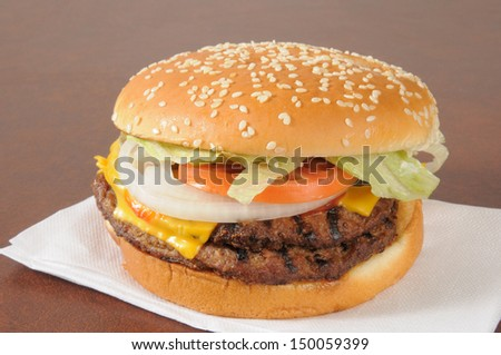 A double cheeseburger with lettuce, pickles, tomatoes and a sesame seed bun