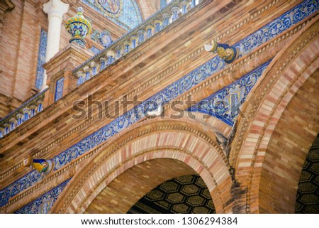 A dove visits the beautiful tiled arches of the Plaza de Espana in Seville #1306294384