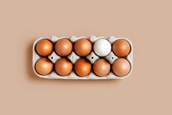A dozen eggs in a box on the table with one white egg, top view. Minimalistic product concept