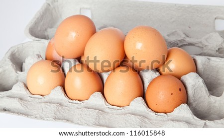 A dozen eggs piled in the carton.