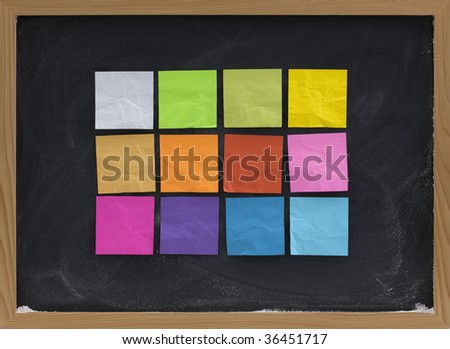 a dozen of blank, colorful sticky notes on a blackboard with white chalk smudges
