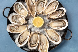 A dozen of oysters with a lemons, close-up overhead shot