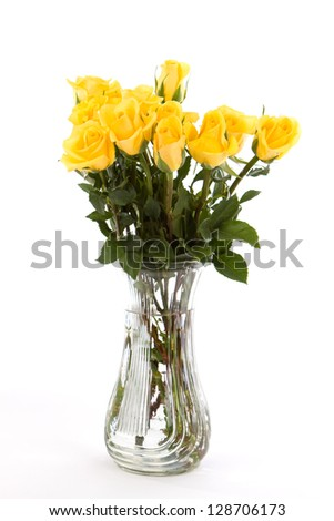 A dozen yellow friendship roses in a vase against a white background.